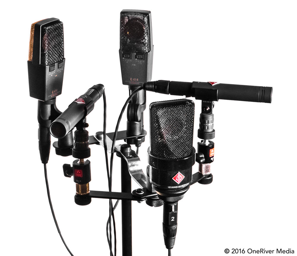 This microphone setup is based on different mics and polar patterns, while stile maintaining exact pairs (in fact, the L/R and Ls/Rs pairs shown are factory matched pairs). All the mics and parts to build this surround tree were used with available mics/parts that we already had. Note that the microphone bar mounts are three bars placed together (one 3-point up front and two 2-point mounts in the middle/back). The ball heads were used on the L/R mics to position the capsules at the same height as the center mic. Mics are as follows: L/R = Neumann KM 184 Matched Pair, C = Neumann TLM 103, Ls/Rs = AKG C414 XL II Matched Pair.